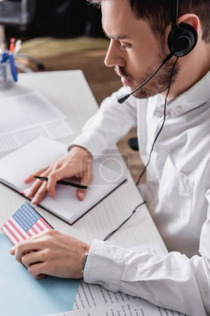 young interpreter in headset holding pen and digital translator with usa flag emblem, blurred background