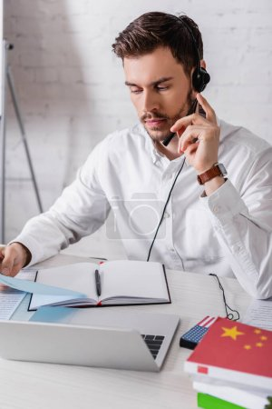 young interpreter in headset holding document near digital translator and dictionaries on blurred foreground