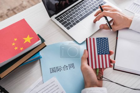 """partial view of interpreter holding digital translator near paper with chinese hieroglyphs. Translation: """"international contract"""""""