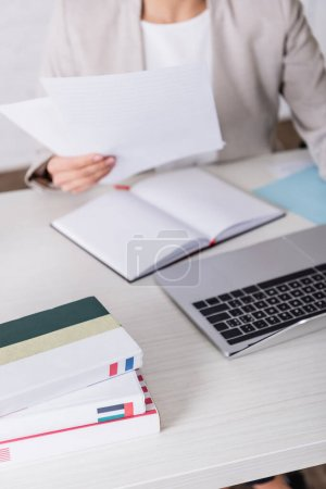 cropped view of translator holding documents near blank notebook, laptop, and dictionaries, blurred background
