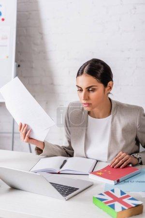 traductor concentrado sosteniendo documento cerca de cuaderno vacío y portátil