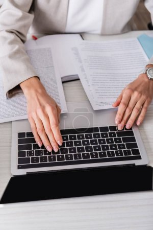 partial view of translator typing on laptop near documents in office