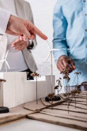Foto de Vista recortada del empresario apuntando a la estación de energía verde con generadores eólicos cerca de socios multiculturales, enfoque selectivo - Imagen libre de derechos
