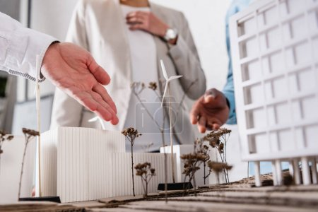 Photo pour Vue recadrée d'un homme d'affaires pointant vers une station d'énergie alternative proche d'un modèle de construction et de partenaires multiethniques sur fond flou - image libre de droit