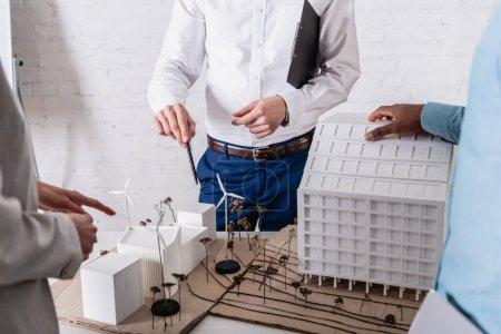 Photo pour Vue partielle des partenaires commerciaux pointant vers le modèle de station d'énergie propre près d'un homme d'affaires afro-américain, premier plan flou - image libre de droit