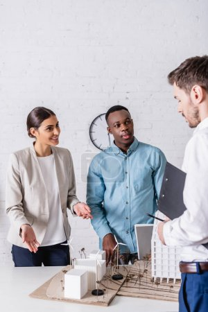 Lächelnde Geschäftsfrau zeigt auf Modell einer grünen Energiestation in der Nähe multiethnischer Geschäftspartner