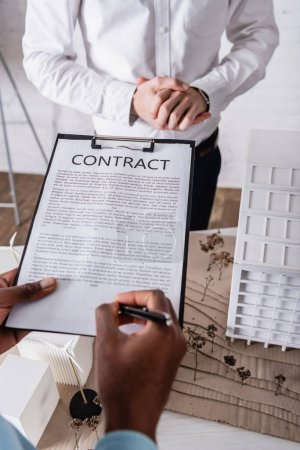 Photo for Partial view of african american businessman signing contract near business partner and green power station model, blurred background - Royalty Free Image