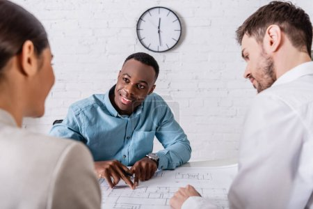 smiling african american businessman pointing at blueprint while looking at business partner near translator on blurred foreground