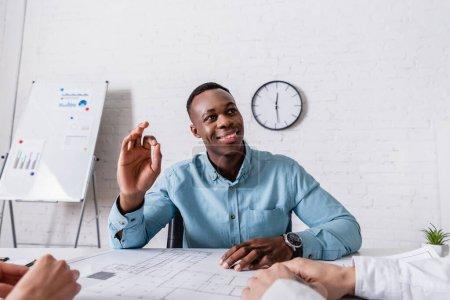 Photo pour Homme d'affaires afro-américain joyeux montrant un geste correct près du plan directeur et des partenaires d'affaires au premier plan - image libre de droit
