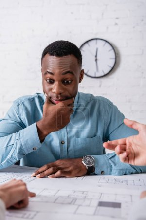 discouraged african american businessman looking at blueprint near business partners gesturing on blurred foreground