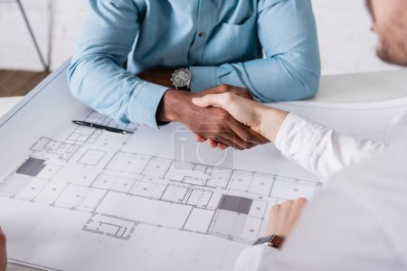 cropped view of african american businessman shaking hands with business partner near blueprint, blurred foreground
