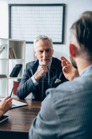 Photo pour Investisseur dans l'habillement formel regardant homme d'affaires sur le premier plan flou près d'un ordinateur portable au bureau - image libre de droit