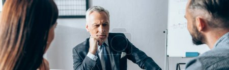 Photo for Mature investor looking at businesspeople on blurred foreground in office, banner - Royalty Free Image