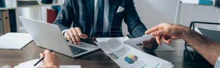 Cropped view of businessman pointing with finger near papers with charts, colleague with pen and investor using laptop on blurred background in office, banner