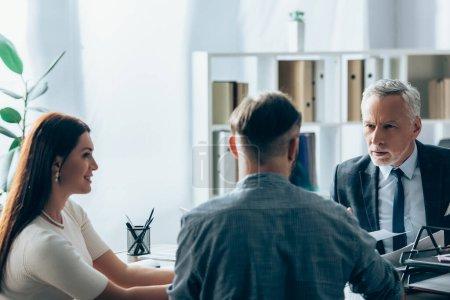 Photo pour Investisseur parlant avec un homme d'affaires près d'une femme d'affaires souriante au premier plan flou - image libre de droit