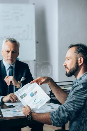 Businessman holding paper with charts near investor on blurred background in office