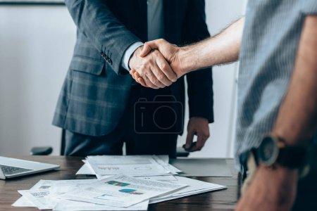 Photo pour Vue recadrée de la poignée de main des investisseurs avec un homme d'affaires au premier plan flou près d'un ordinateur portable et des papiers au premier plan flou - image libre de droit