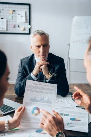 Mature investor looking at business partners with documents on blurred foreground