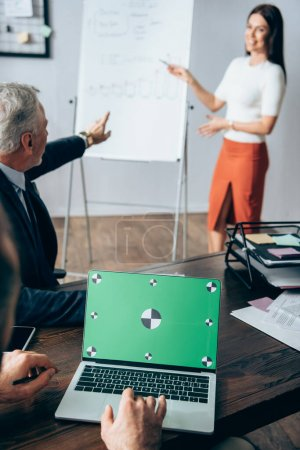 Businessman using laptop with chroma key near near investor pointing at flipchart and businesswoman on blurred background in office