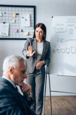 Photo pour Femme d'affaires inquiète montrant arrêt près de tableau à feuilles mobiles et investisseur mature sur le premier plan flou - image libre de droit