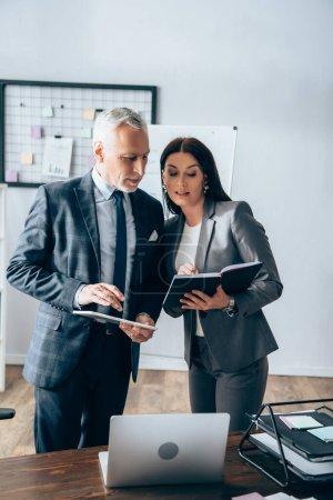Geschäftsfrau zeigt auf Notizbuch neben Investor mit digitalem Tablet und Laptop auf Bürotisch