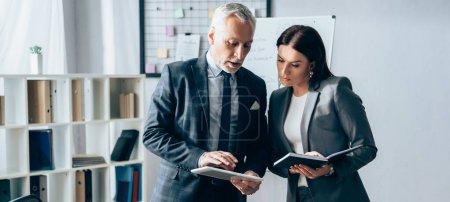 Mature investor using digital tablet near businesswoman with notebook in office, banner