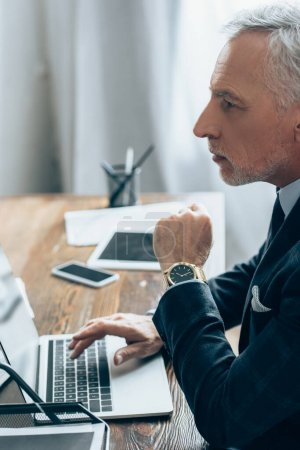 Photo for Investor in suit using laptop near devices on blurred background in office - Royalty Free Image