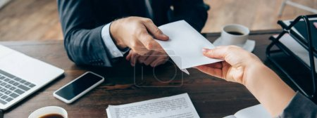 Photo for Cropped view of businesswoman taking envelope from investor near coffee and devices on table, banner - Royalty Free Image