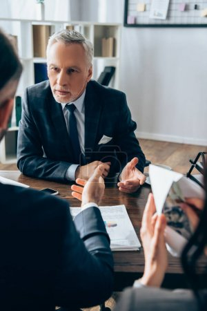 Mature investor talking at businessman near colleague with money and envelope on blurred foreground