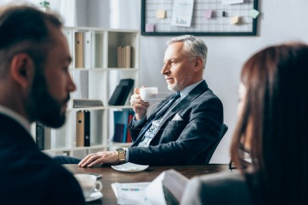 Mature investor holding coffee cup near business people on blurred foreground in office
