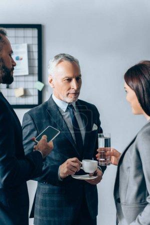 Photo pour Femme d'affaires avec verre d'eau debout près des hommes d'affaires avec café et smartphone dans le bureau - image libre de droit