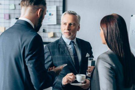 Photo pour Conseiller mature avec une tasse de café en regardant un homme d'affaires avec un smartphone et une femme d'affaires avec un verre d'eau au premier plan flou - image libre de droit