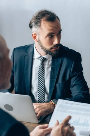 Photo for Businessman using laptop near advisor pointing at paper on blurred foreground - Royalty Free Image