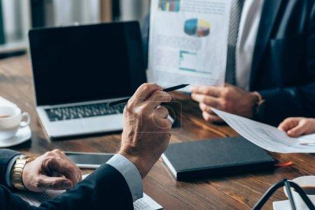 Foto de Vista recortada del inversor apuntando a gente de negocios con documentos cerca de dispositivos en un fondo borroso - Imagen libre de derechos
