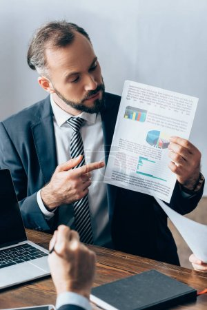 Businessman pointing at paper with charts near laptop, investor and colleague on blurred foreground