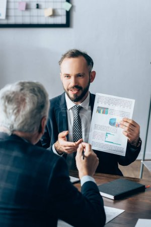 Businessman showing paper with graphs near mature investor on blurred foreground