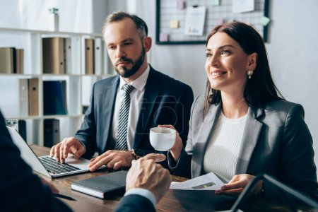 Photo for Smiling businesswoman holding cup near colleague using laptop and investor pointing with finger on blurred foreground - Royalty Free Image