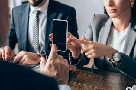 Photo for Cropped view of businesswoman pointing at smartphone with blank screen near colleague and investor on blurred foreground - Royalty Free Image