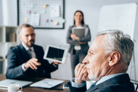 Pensive investor sitting near business people on blurred background in office