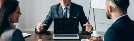 Smiling advisor pointing at laptop near business partners with coffee on blurred foreground, banner