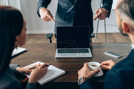 Photo for Investor pointing with fingers at laptop with blank screen near colleagues with coffee and notebook on blurred foreground - Royalty Free Image