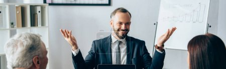 Photo for Cheerful businessman pointing with hands near colleagues on blurred foreground in office, banner - Royalty Free Image