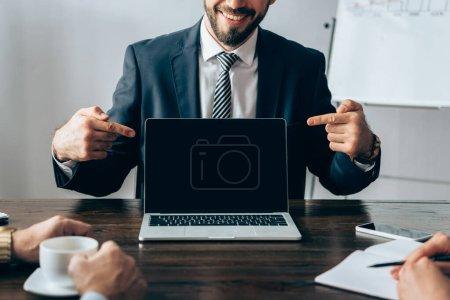 Ausgeschnittene Ansicht eines lächelnden Geschäftsmannes, der auf Laptop mit leerem Bildschirm zeigt, in der Nähe von Partnern mit Kaffee und Notizbuch im Büro