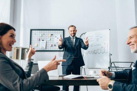 Photo pour Homme d'affaires souriant pointant du doigt ses collègues sur un avant-plan flou près d'un tableau à feuilles mobiles au bureau - image libre de droit