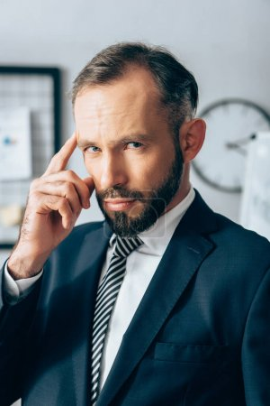 Businessman in formal wear looking at camera and pointing with finger at head in office