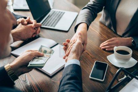 Photo pour Homme d'affaires tenant de l'argent et serrant la main d'un collègue près du smartphone et du café sur la table - image libre de droit