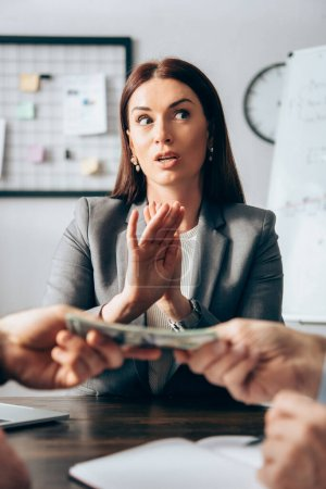 Photo for Businesswoman showing stop gesture near colleagues holding money on blurred foreground - Royalty Free Image