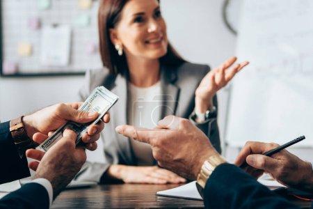 Homme d'affaires pointant vers dollars près collègue et femme d'affaires sur fond flou