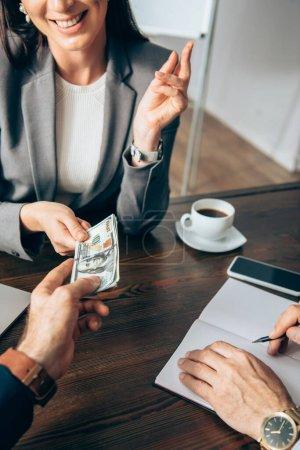 Photo pour Vue recadrée d'un homme d'affaires donnant de l'argent à une femme d'affaires souriante près d'un collègue avec un cahier - image libre de droit
