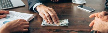 Photo pour Vue recadrée de l'homme d'affaires tenant des dollars près des partenaires avec des papiers sur le premier plan flou, bannière - image libre de droit